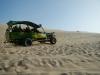 Een buggy raced met toeristen over de duinen