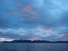 De zon kleurt tijdens zijn ondergang de onderkant van de wolken roze